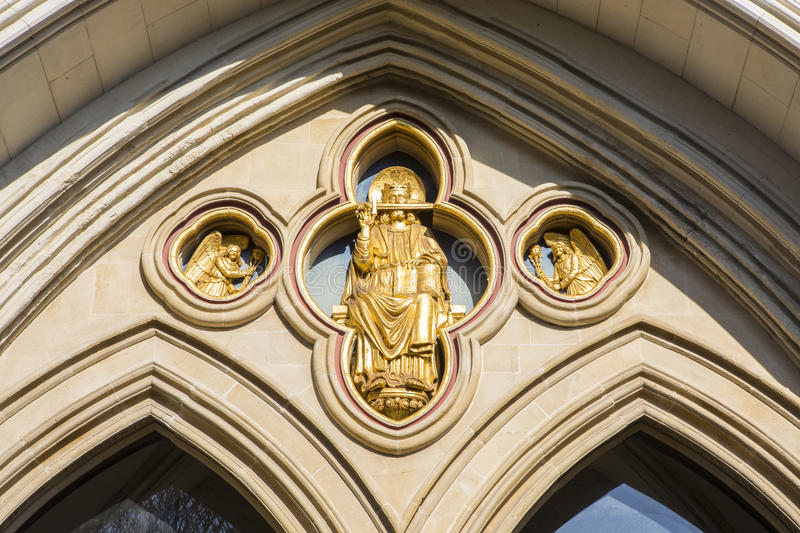 Saint Richard Sculpture at Chichester Cathedral in Sussex. A golden sculpture of Saint Richard of Chichester above the western entrance of Chichester Cathedral royalty free stock photo