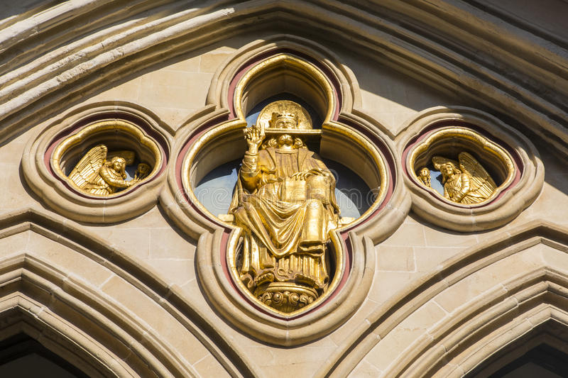Saint Richard Sculpture at Chichester Cathedral in Sussex. A golden sculpture of Saint Richard of Chichester above the western entrance of Chichester Cathedral royalty free stock photos