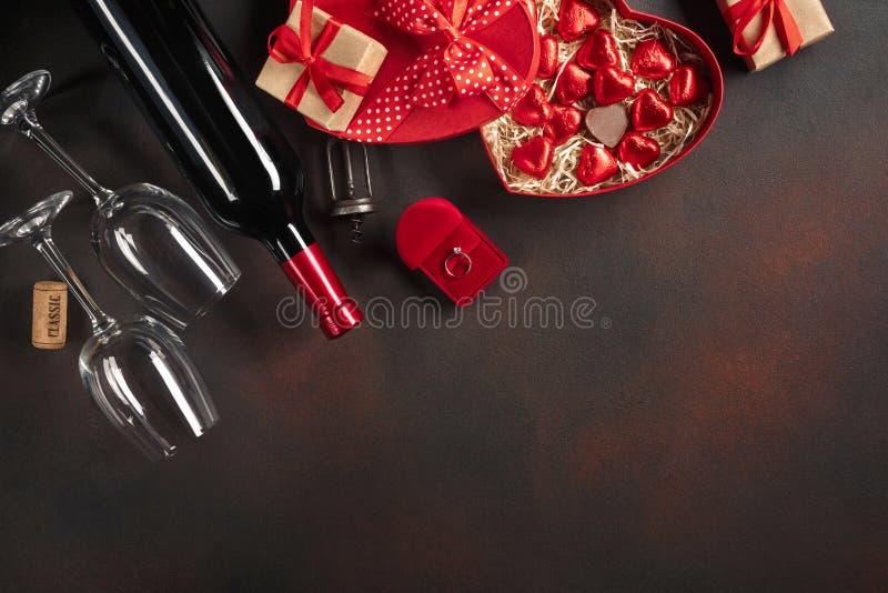 Saint-Valentin avec les coeurs, le vin, le tire-bouchon, les verres, les cadeaux, une boîte en forme de coeur et un tableau noir photographie stock