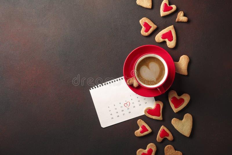 Saint-Valentin avec une tasse de café, d'un biscuit en forme de coeur et d'un calendrier photo stock