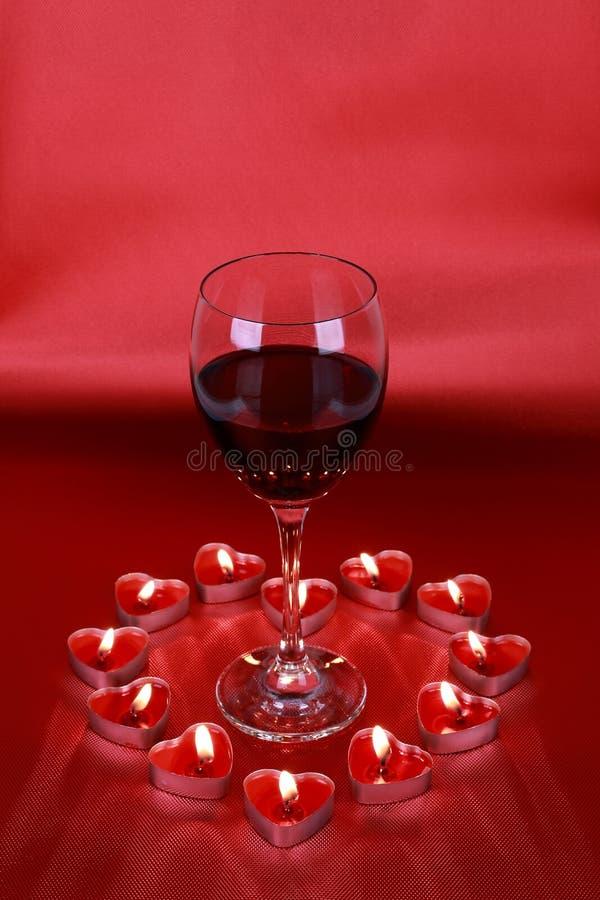 Saint-Valentin, verre de vin avec les bougies en forme de coeur sur le fond rouge photo libre de droits