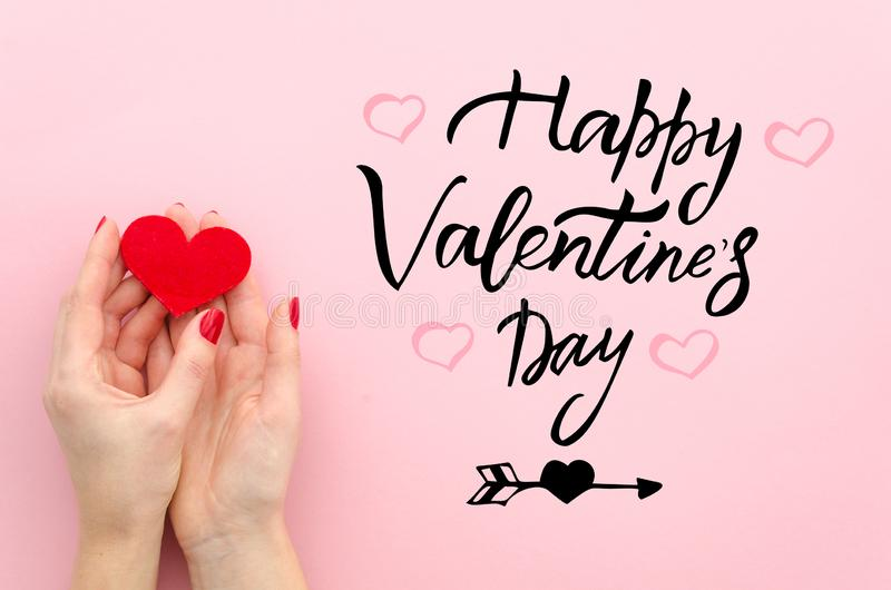 Saint Valentine concept. Flat lay female hands hold red heart and congratulation inscription on pink background. Top royalty free stock photos
