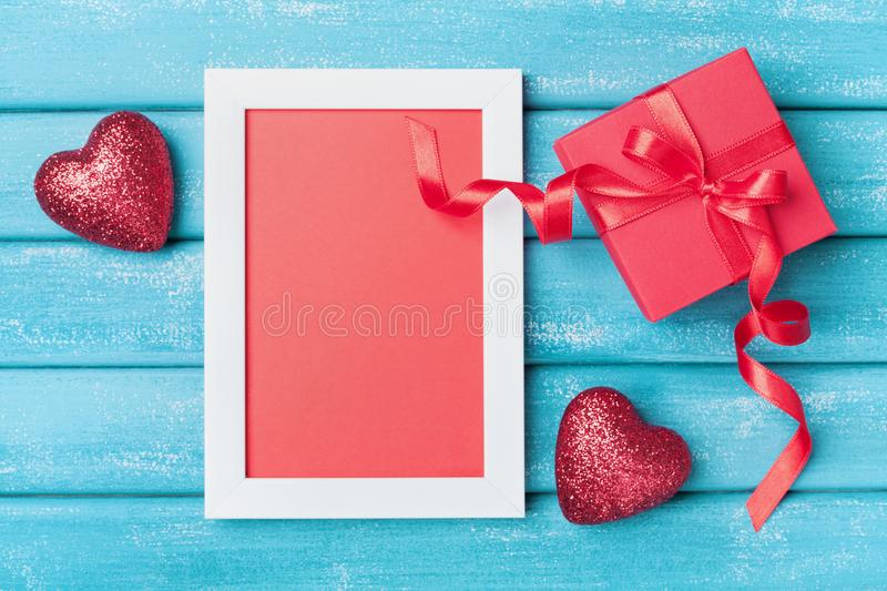 Saint valentine day greeting card. Frame, gift box and red heart on turquoise wooden background top view. Saint valentine day greeting card. Frame, gift box and royalty free stock images