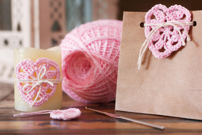 Saint Valentine decoration: handmade crochet pink heart for candle and gift package stock image
