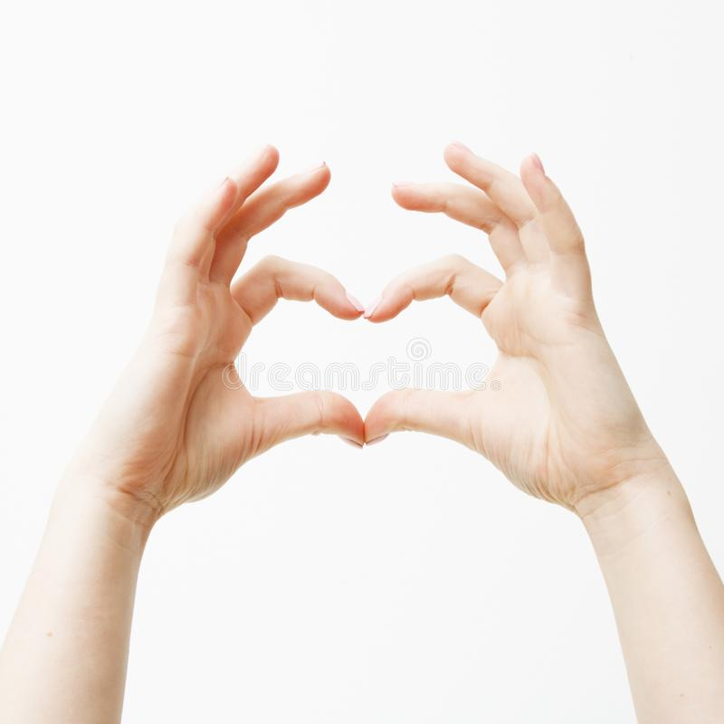Saint Valentines Day. Minimal style. Close up of two female caucasian hands isolated on white background. Young woman. Forming shape of heart with her fingers royalty free stock photos