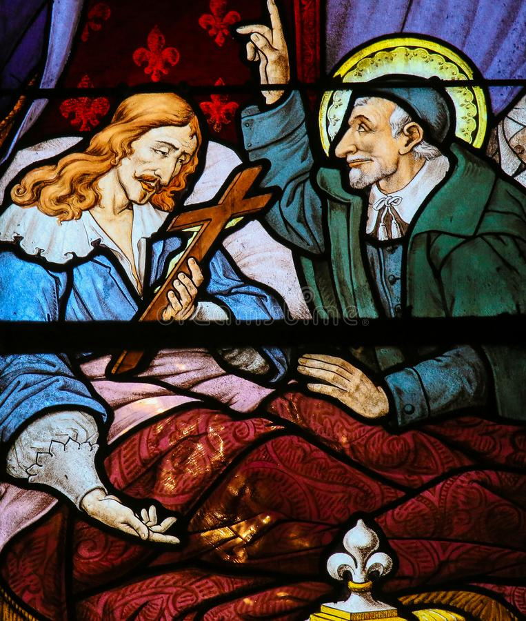 Saint Vincent de Paul on a Stained Glass in Paris royalty free stock photos