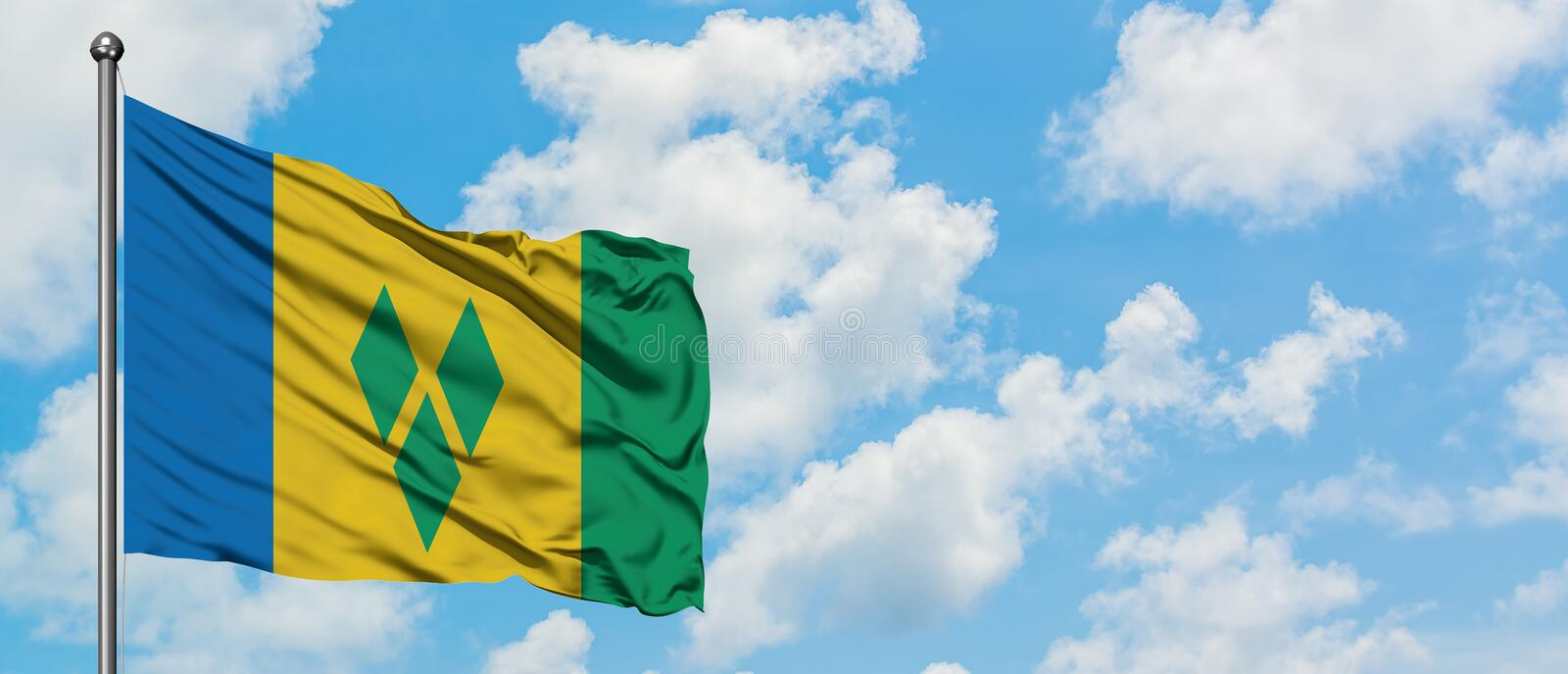 Saint Vincent And The Grenadines flag waving in the wind against white cloudy blue sky. Diplomacy concept, international relations.  stock photography