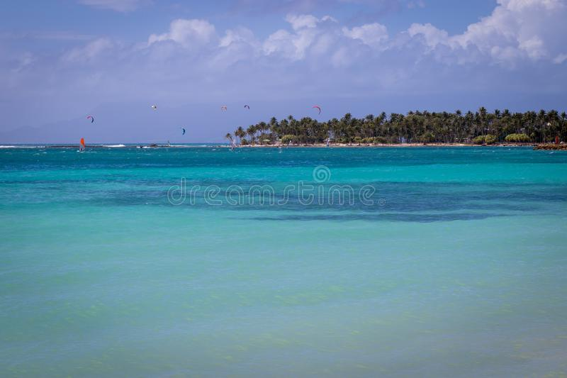 Sainte-Anne bay and beach. Windsurfers and kitesurfers enjoying the sport in backgro. Turquoise and crystal clear sea in Guadeloupe, Sainte-Anne bay and beach stock images
