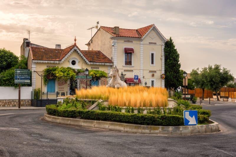 Saintes-Maries-de-la-Mer, Francia - 19 de julio de 2017: Pequeña ciudad mediterránea, anillo del camino adornado con la hierba y  imágenes de archivo libres de regalías