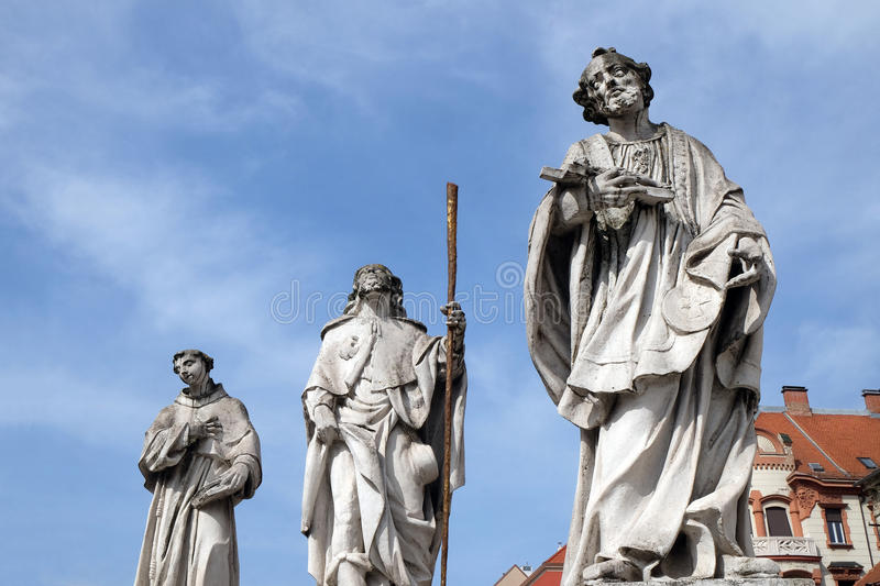 Saints Anthony of Padua, Roch and Francis Xavier. Statue, Plague column at Main Square of the city of Maribor in Slovenia, Europe. Historical religious royalty free stock photo
