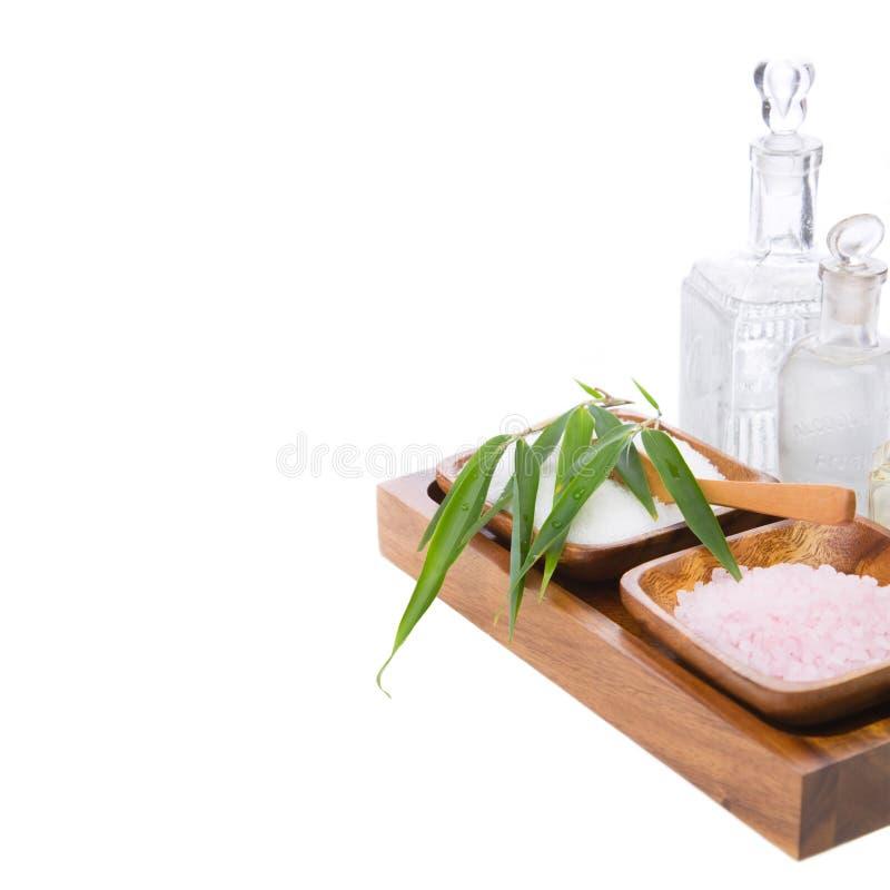 Sais de banho e óleos da massagem com as toalhas isoladas no branco foto de stock
