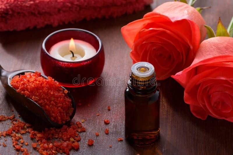 Sais de banho minerais, óleo essencial, vela e flores fotografia de stock royalty free