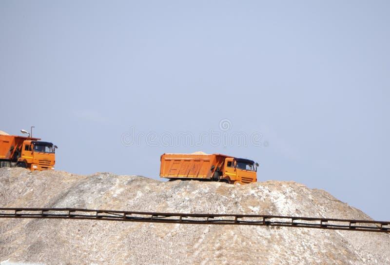 sais do potássio e do magnésio Grande máquina da máquina escavadora e montanhas enormes do minério waste na extração de p fotos de stock