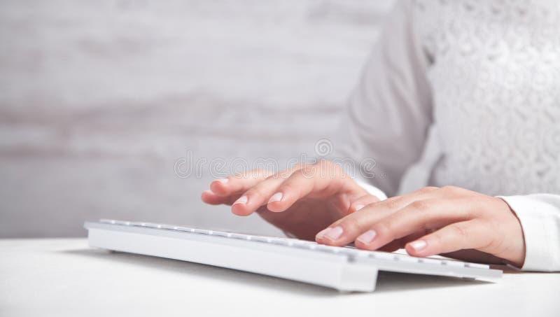 Saisie de filles sur le clavier d'ordinateur dans le bureau photographie stock libre de droits