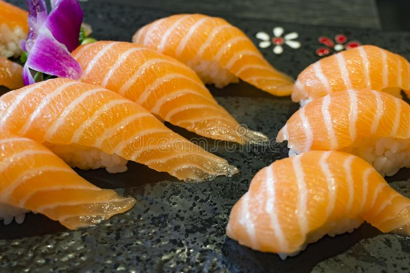 Saké de sushi un plat en pierre noir photographie stock