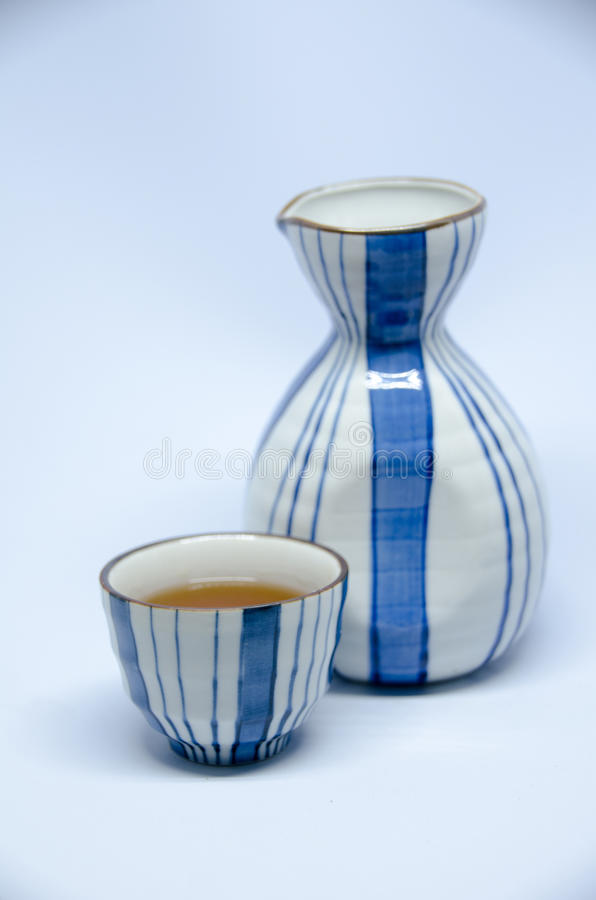 Sake bottle and cup on bright white background. Isolated image object stock photo