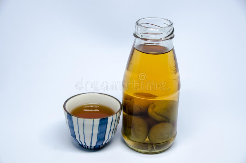 Sake bottle and cup on bright white background. Umeshu royalty free stock images