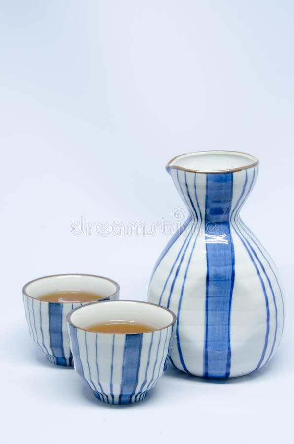 Sake bottle and cup on bright white background. Sake bottle and cup of umeshu on bright white background royalty free stock images