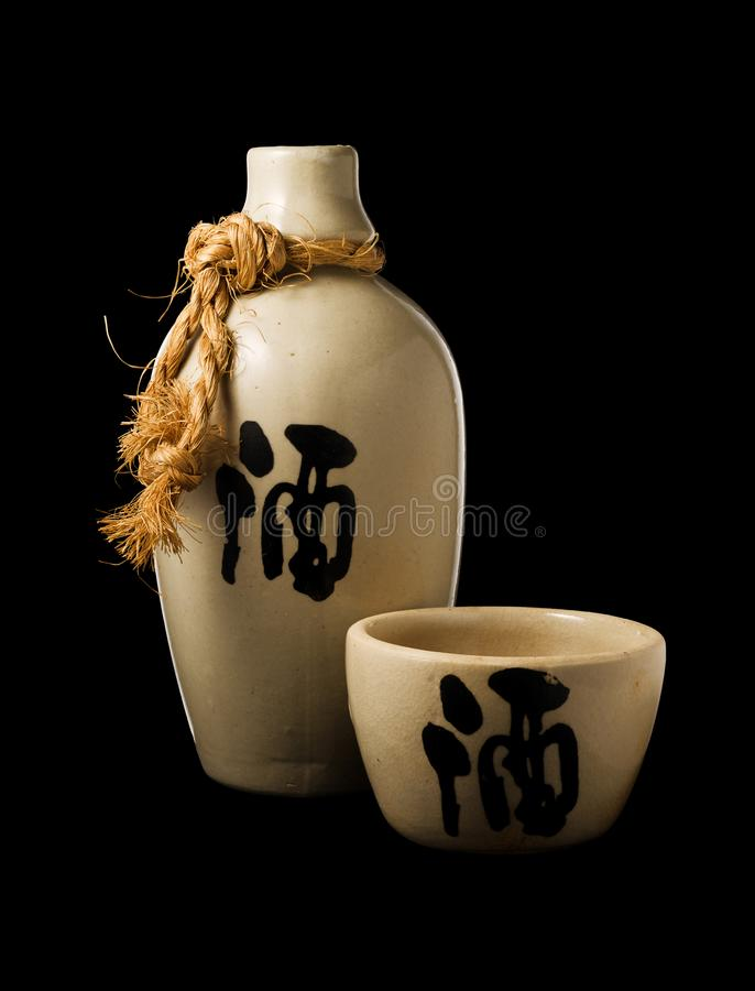 Sake bottle and cup isolated on black background. Sake bottle and cup, with the ideogram for `liquor` on both, isolated on black background with clipping path royalty free stock photo