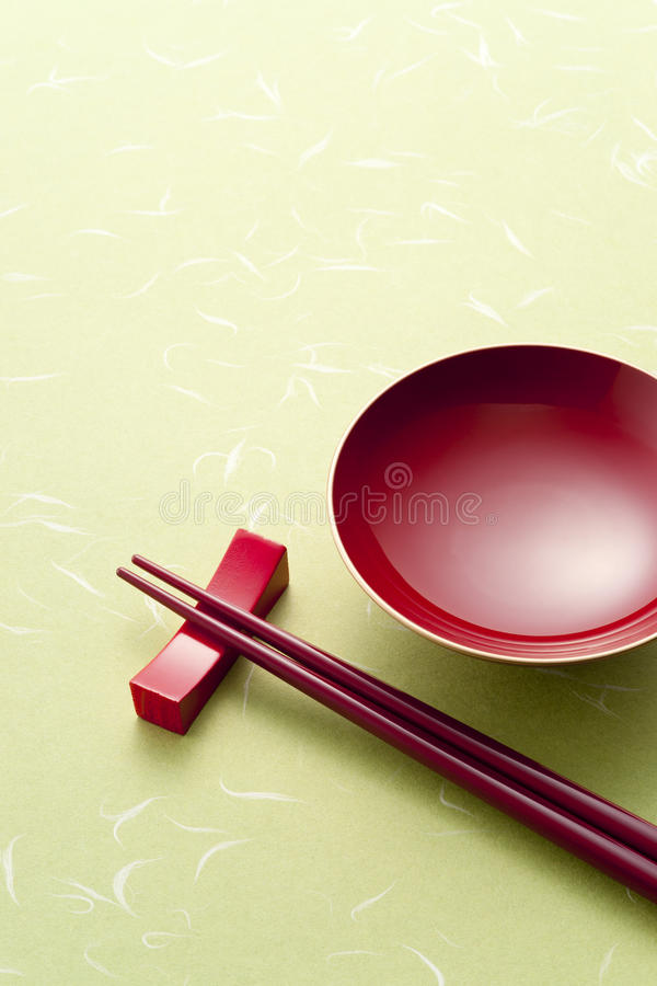 Sake cup. Red sake cup and chopsticks on green japanese paper royalty free stock photography