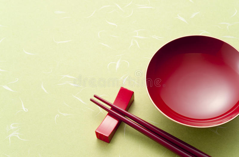 Sake cup. Red sake cup and chopsticks on green japanese paper royalty free stock images