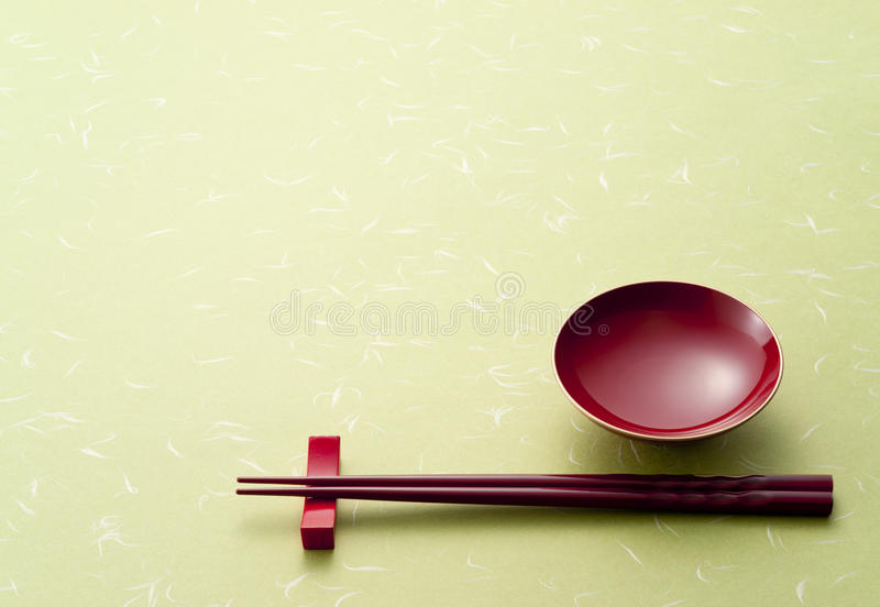 Sake cup. Red sake cup and chopsticks on green japanese paper stock photo