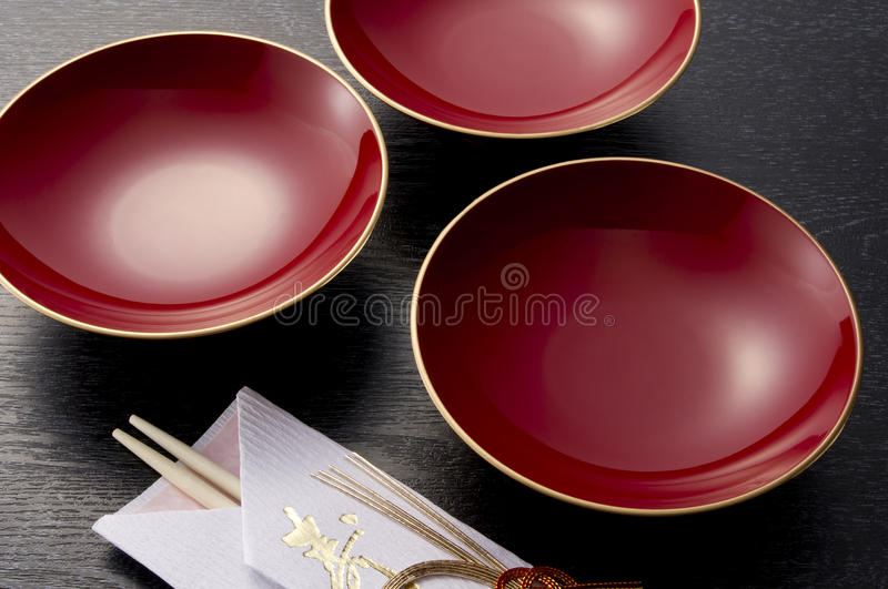 Sake cup. Red sake cup and chopsticks on black background royalty free stock photography