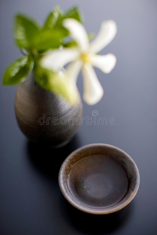 Sake cup and bottle. STILL LIFE-a Japanese sake cup and a bottle with a white flower stock images