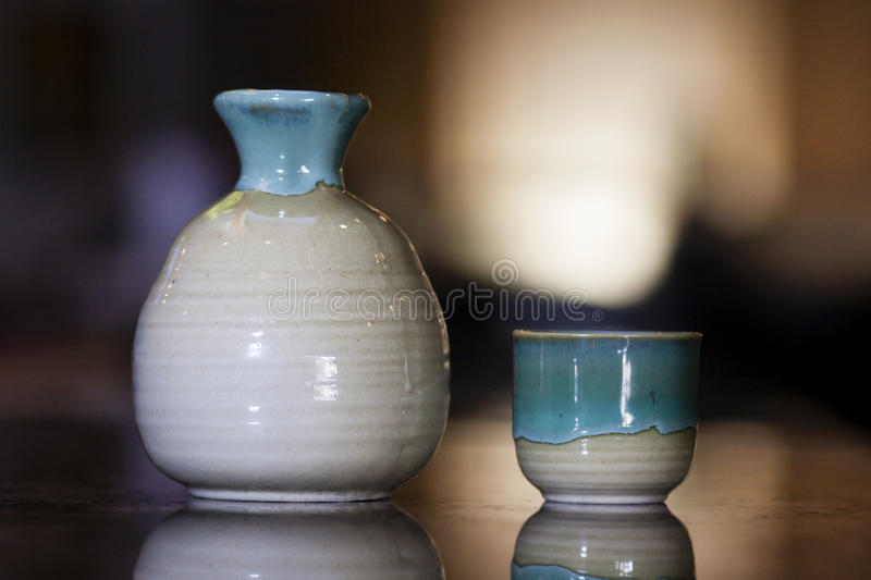 Sake cup and jug. Japanese sake jug and cup on bokeh background royalty free stock image