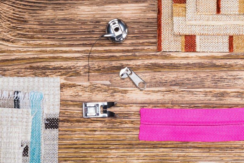 Saker för symaskinen och styckena av kulört tyg, på en mörk träbakgrund arkivbild