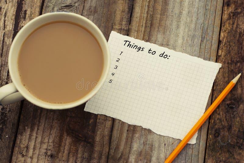 Saker som gör listan, inskrift Tom papper och kopp kaffe, över lantlig träbakgrund som är begreppsmässig arkivfoton