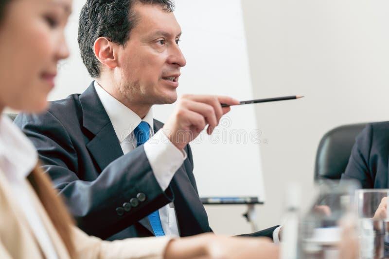 Sakkunnig affärsman som delar hans sikt under ett beslutsfattandemöte royaltyfri bild