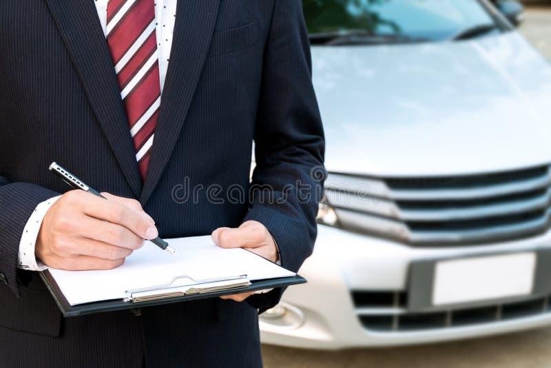 Sakkunnig anställd för försäkring som arbetar med en bil på det utomhus- fotografering för bildbyråer