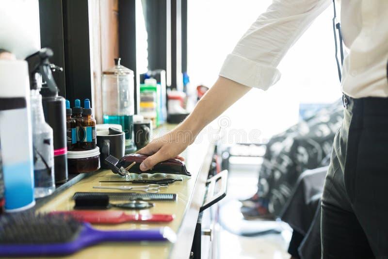 Sakkunnig hållande beskärare för hår på räknare i salong royaltyfri fotografi