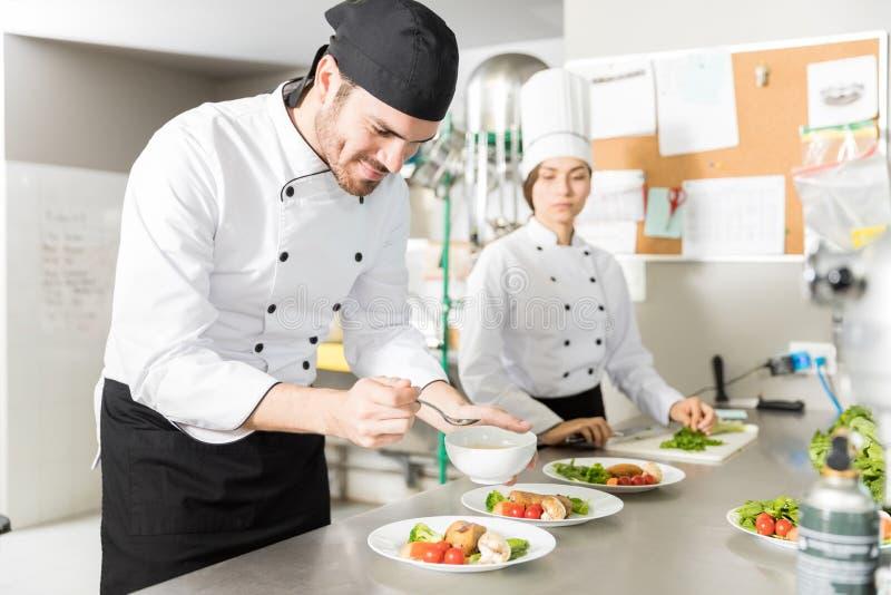 Sakkunnig kockAdding Flavor To maträtt i kök royaltyfri foto