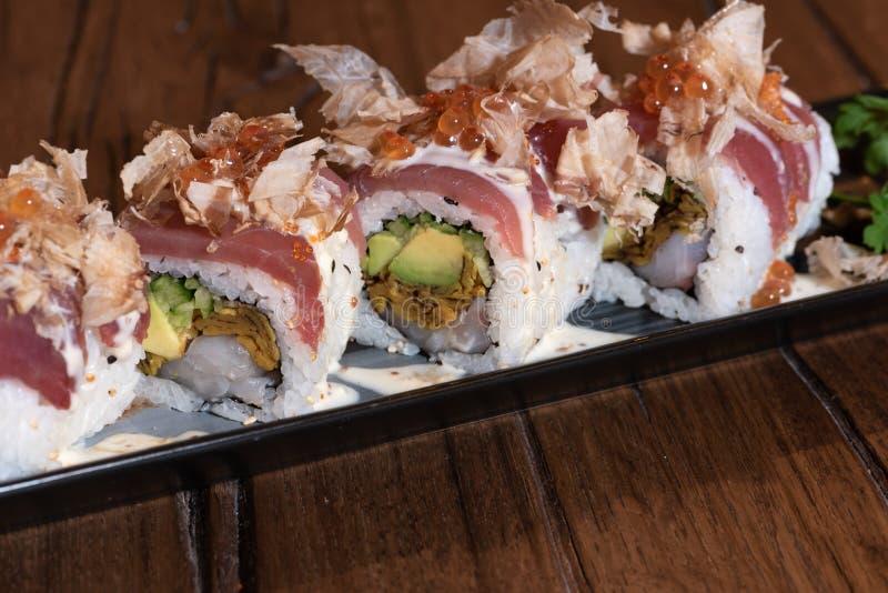 Sakkunnig Uramaki med tonfisk, rå räkor, omelett, ostsås, lökar, Tabasco, kaviar och Katsuobushi royaltyfria foton