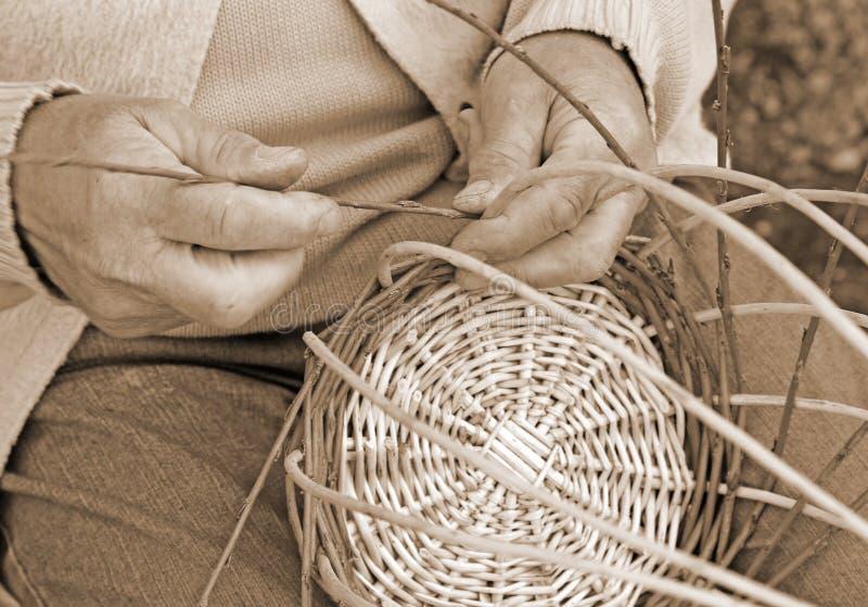 Sakkunniga händer av den äldre hantverkaren skapar vävde vide- bas royaltyfria bilder