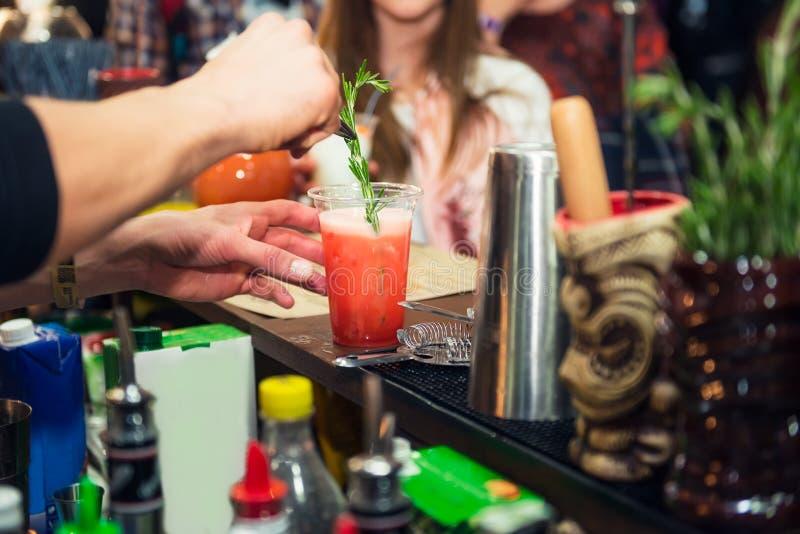 Sakkunniga pro-bartenderhänder gör coctailen och dekorerar drinken med ny rosmarine på färgbakgrunden med folk dricka fotografering för bildbyråer