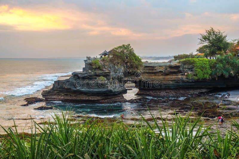 Sakral BalinesetempelTanah lott Pura Batu Bolong på kanten av en klippa på kustlinjen med hålet vaggar in royaltyfri foto