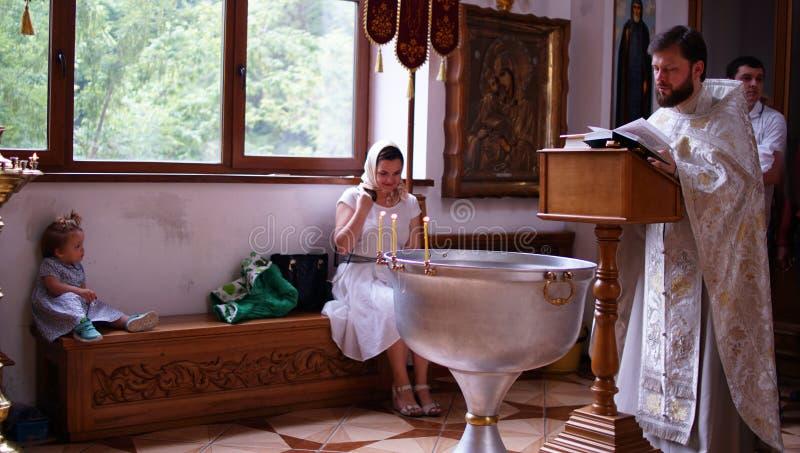 Sakramentet av dopet Att döpa behandla som ett barn Barn, präst och församlingsboer arkivbilder