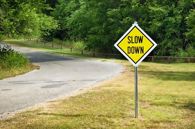 Sakta ner gult trafiktecken arkivfoton
