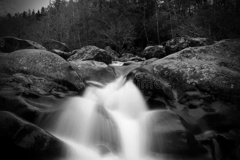 Saktar suddig rörelse för gråskalan och slutareWaterscape fotografi av en vattennedgång över stora stenar arkivbilder