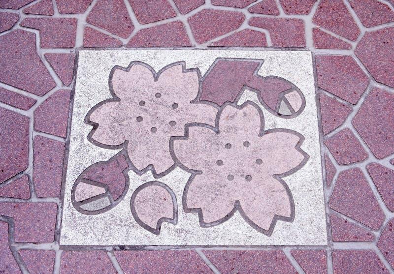 Sakurabeeld op de vloertegels van voetbrug op Yasukuni-dori in Chiyoda, Tokyo, Japan stock afbeelding