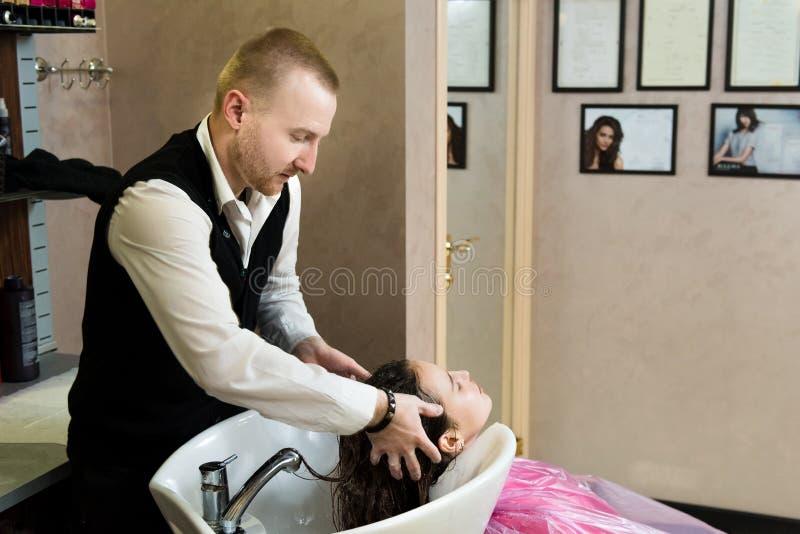 Salão de beleza, cuidados capilares e conceito dos povos - o cabeleireiro entrega a cabeça feliz de lavagem da jovem mulher imagem de stock royalty free