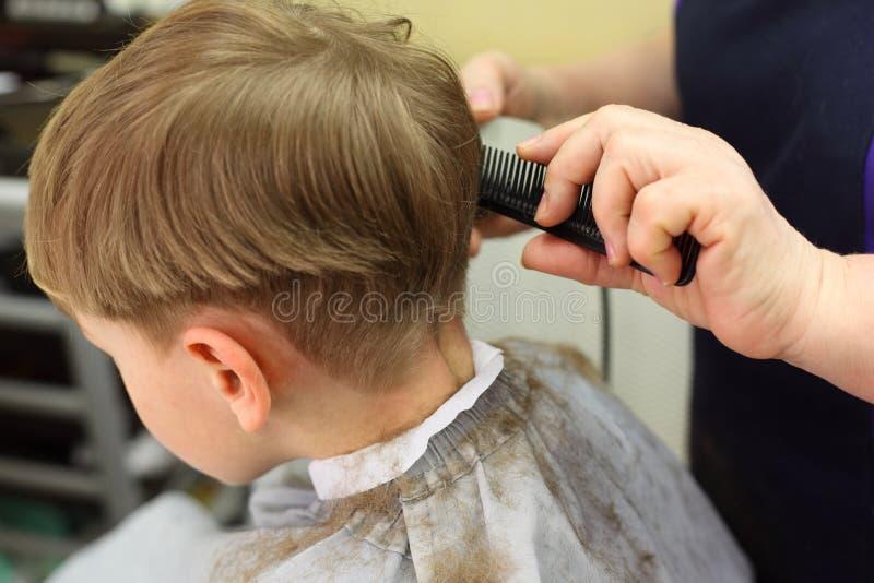 Salão de beleza dentro cortado menino do hairdressing imagens de stock royalty free