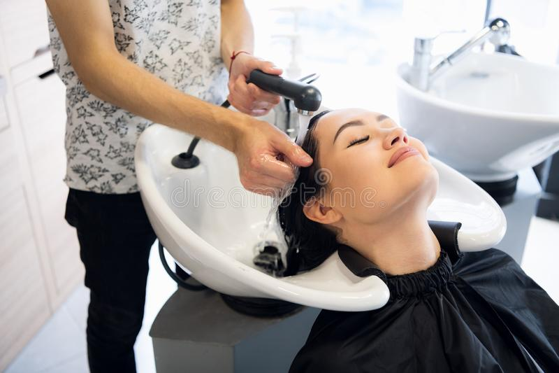 Salão de beleza do cabeleireiro Mulher moreno bonita durante a lavagem do cabelo foto de stock