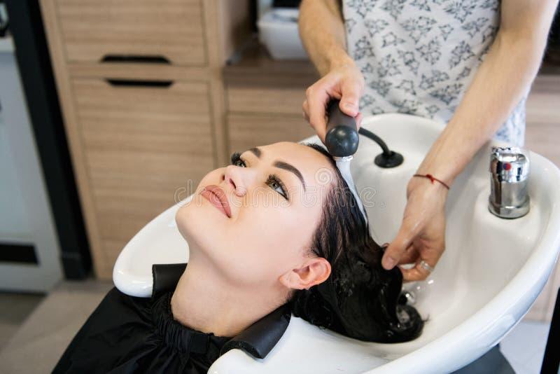 Salão de beleza do cabeleireiro Mulher moreno bonita durante a lavagem do cabelo fotografia de stock