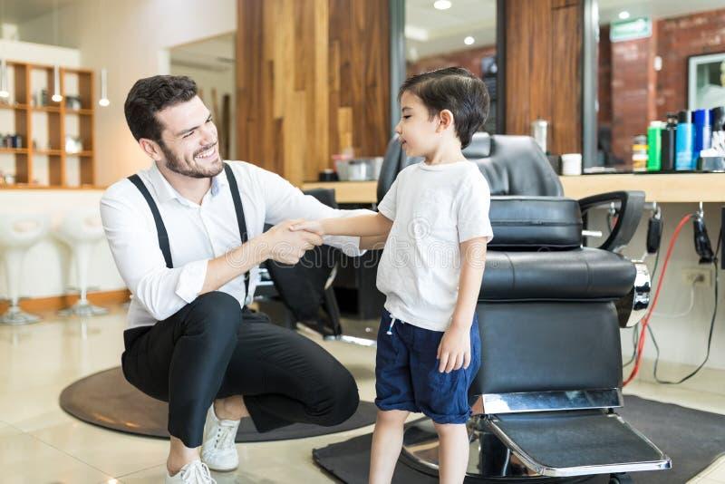 Salão de beleza masculino de sorriso de Barber Greeting Little Customer In imagens de stock royalty free