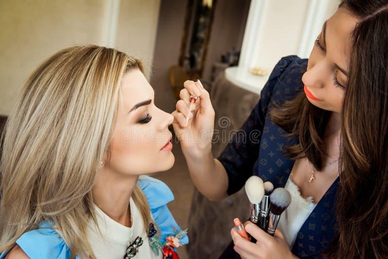 Salón de belleza, el maquillaje del dklayut de la muchacha y el diseñar en el salón, los peluqueros y el artista de maquillaje imagen de archivo