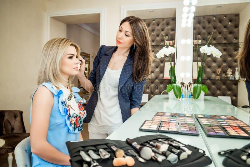 Salón de belleza, el maquillaje del dklayut de la muchacha y el diseñar en el salón, los peluqueros y el artista de maquillaje imágenes de archivo libres de regalías
